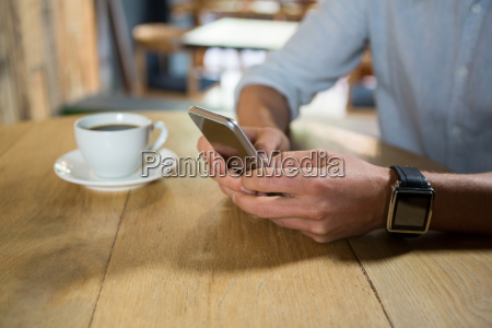 man using mobile phone at table