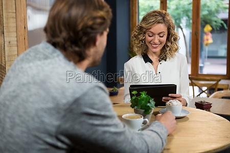 man looking at woman using digital