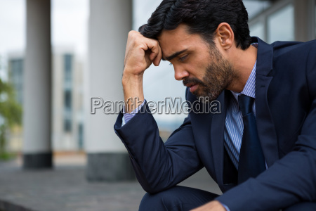 depressed businessman sitting with hand on
