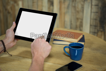 man using digital tablet in coffee
