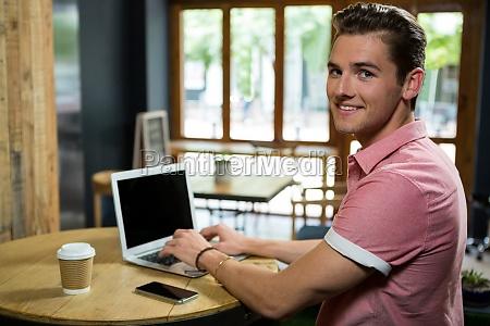 smiling young man using laptop at