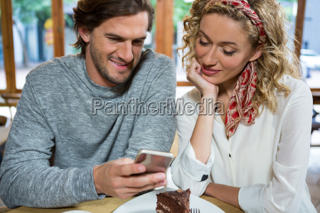smiling couple using smart phone at