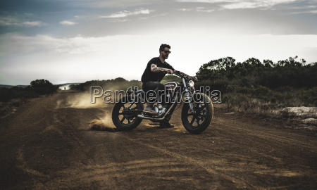 man wearing sunglasses riding cafe racer