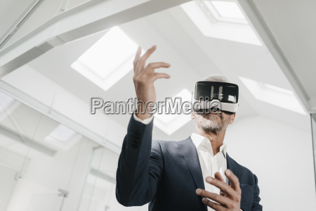mature businessman in office wearing vr