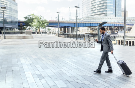 businessman walking through the city with