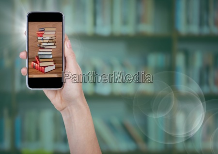 hand with phone showing book pile