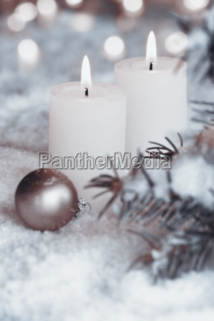 burning candles in snow