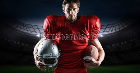 american football player holding rugby ball
