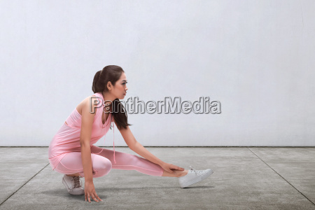 sporty asian woman doing stretching before