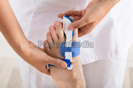 orthopedist fixing plaster on injured mans