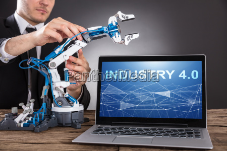 businessman building robot with laptop showing