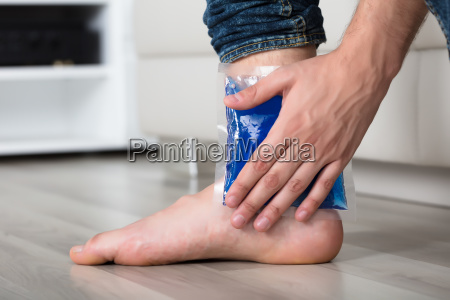 persons hand holding ice gel pack