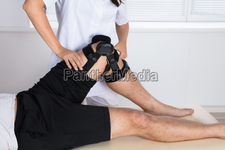 physiotherapist fixing knee braces on mans
