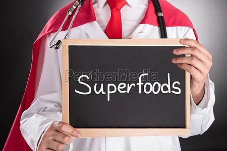 superhero doctor holding small chalkboard
