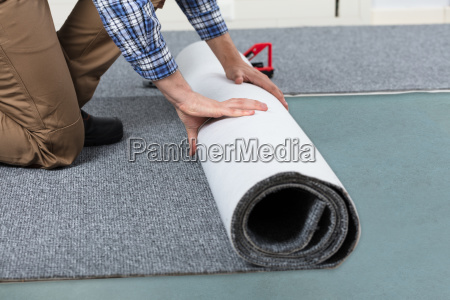 male handyman rolling carpet on floor
