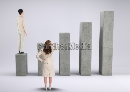 businesswomen standing and looking at graph