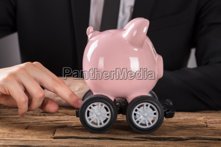 businessperson pushing piggy bank on wheels