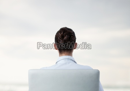 businesswoman in chair facing backwards with