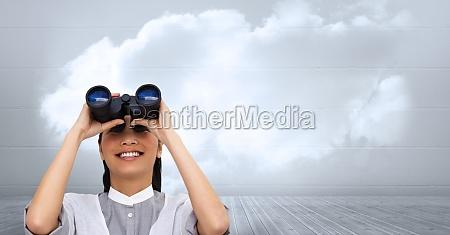 businesswoman using binoculars against cloudy sky