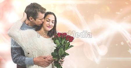 loving man kissing woman holding roses