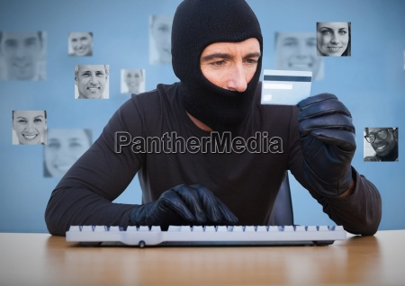 criminal in hood on laptop with