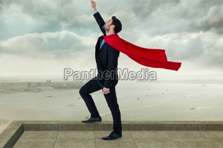 businessman wearing cape with arm raised