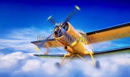 biplane breaks through the clouds