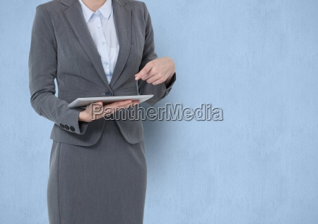 midsection of businesswoman pointing at tablet