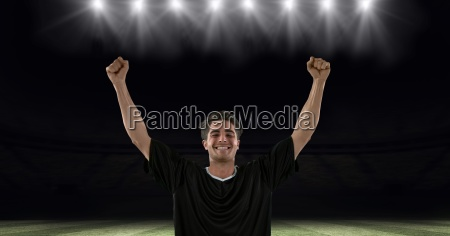 successful soccer player with arms raised