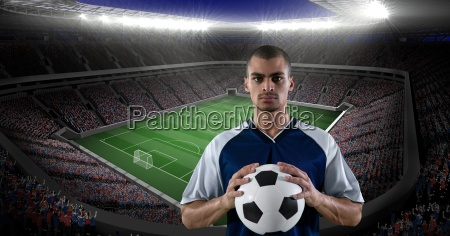 confident player holding soccer ball against
