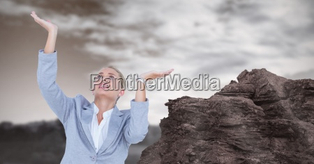 businesswoman with arms raised by rock