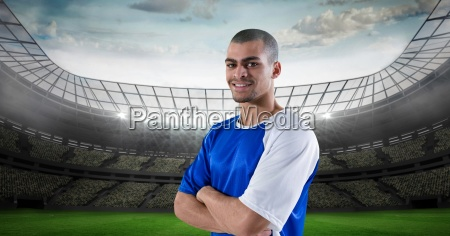 smiling soccer player with arms crossed