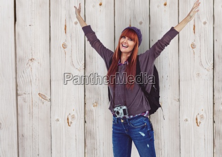 female hipster with arms raised traveling