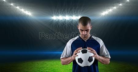 soccer player holding ball at stadium