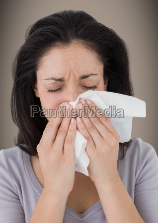 woman crying into tissue against brown