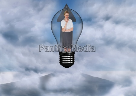 businesswoman standing in bulb against sky