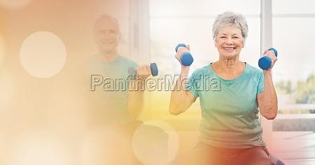 senior man and woman lifting dumbbells