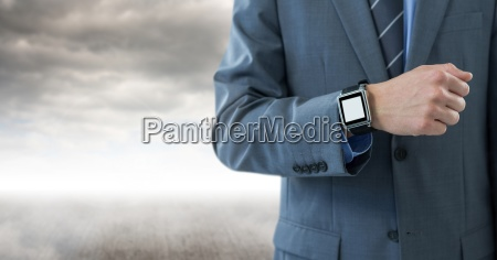 businessman with watch against cloudy background
