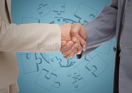 close up of handshake against blue