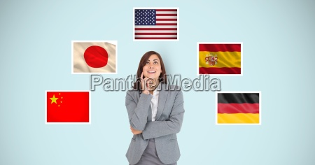 thoughtful businesswoman standing by flags against