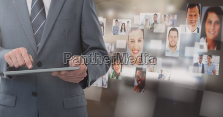 businessman holding tablet with peoples profile