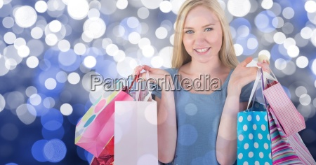 woman holding shopping bags against blue