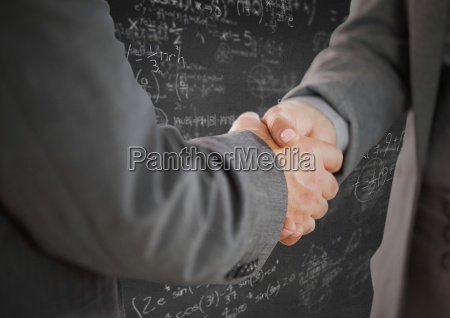 handshake against grey wall with math