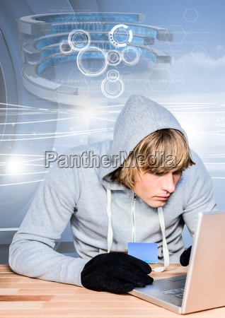 hacker holding a credit card while