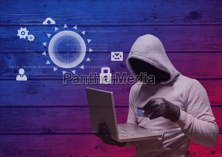 hacker with hood holding a credit