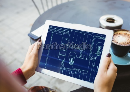 hands with tablet with blueprint on