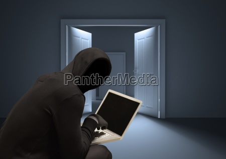 shadow of hacker using a laptop