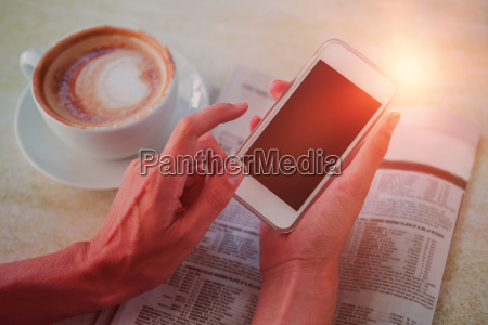 man using mobile phone by coffee