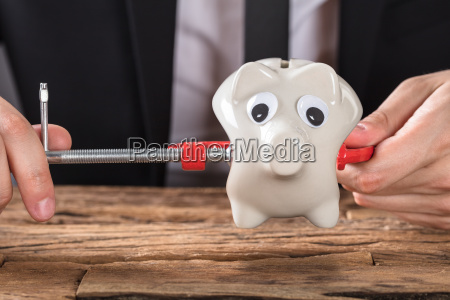 businessperson squeezing piggy bank in clamp