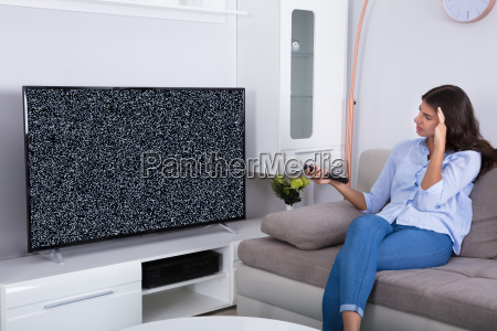 woman getting frustrated with glitch tv